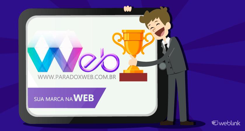 bonequinho segura troféu ao lado do logo do paradoxweb